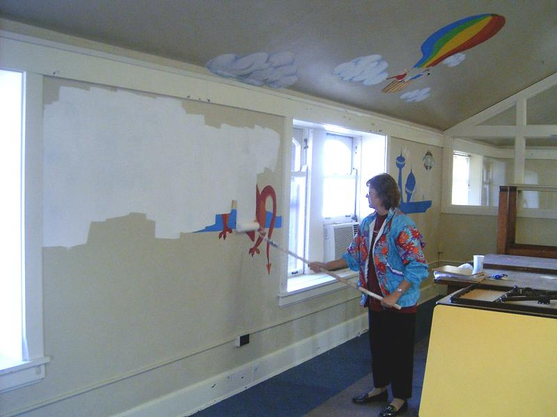 Ruby Moon-Houldson painting over the mural in the upstairs room that used to house the child's library
