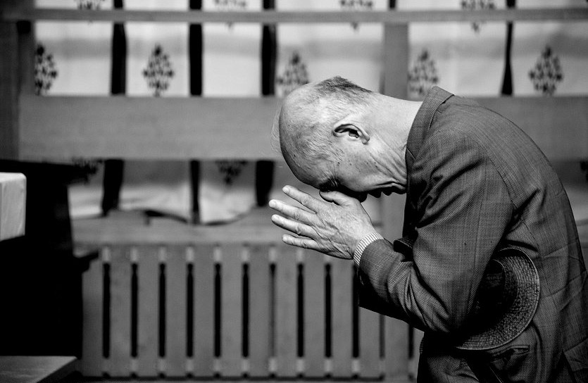 A man praying at a Japanese Shintō shrine.