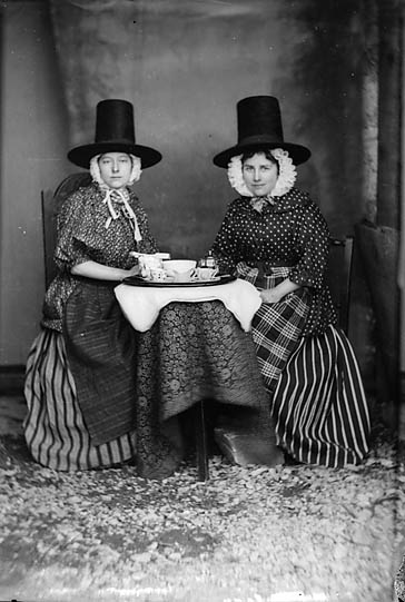 Two women in national dress drinking tea (Jones) NLW3363089