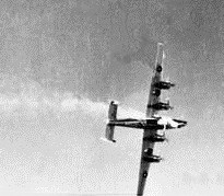 Underside view of four-engined military aircraft trailing flames from its forward fuselage