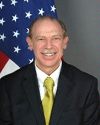 Full frontal photo of a white man's face and torso, smiling, with white mustache, blondish receding hair, slightly prominent ears, yellow necktie in half windsor, white shirt, dark suit, in front of American flag.