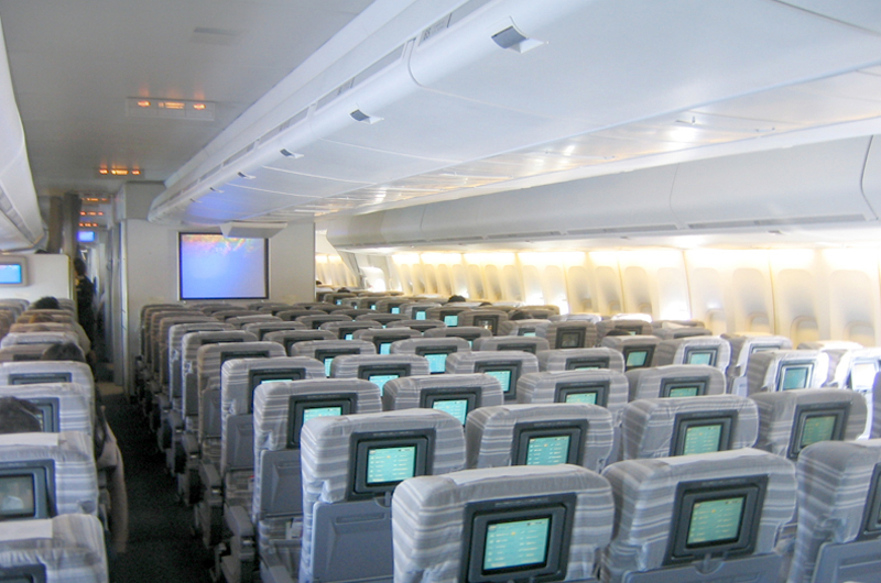 Interior view. Seats are separated by two aisles, in 3–4–3 configuration. A TV is positioned towards the front of aircraft.