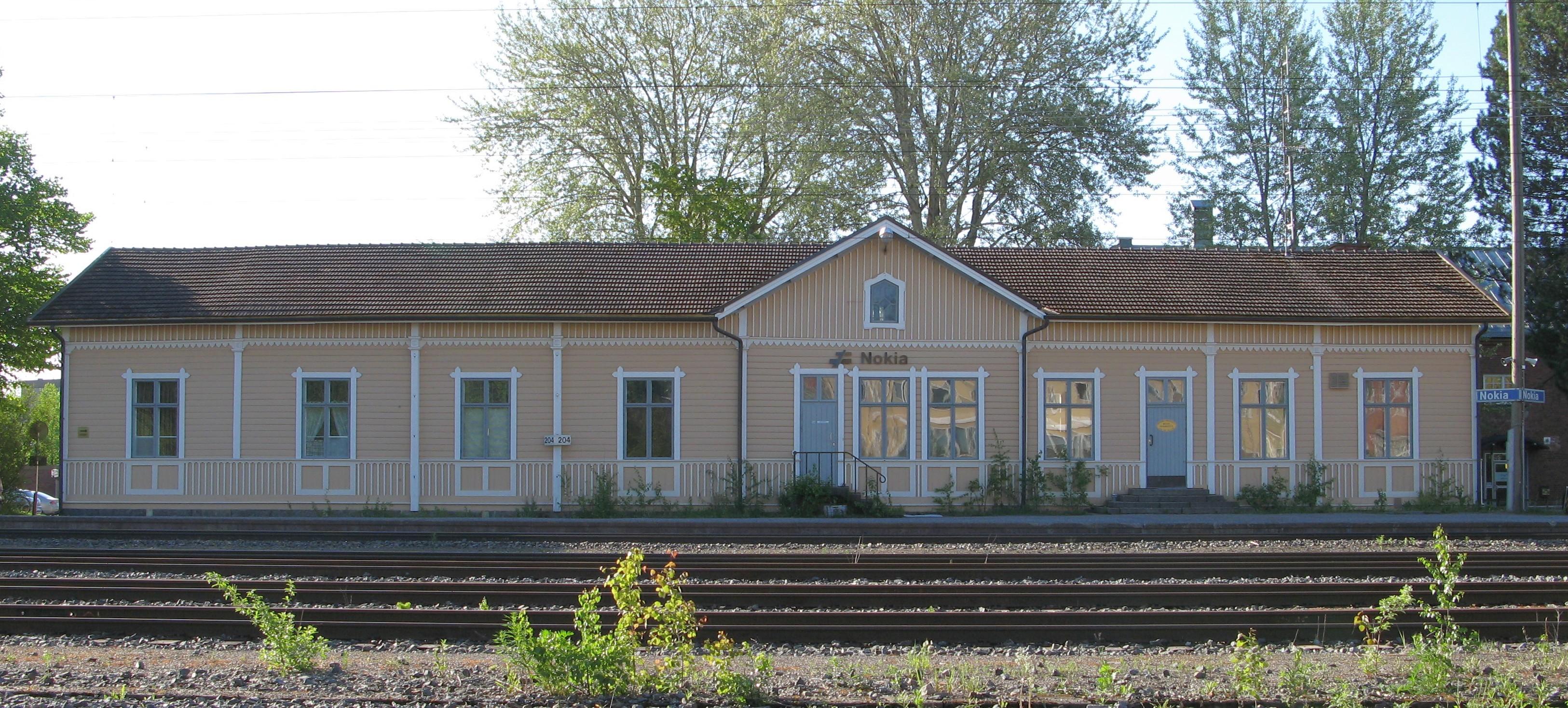 Kesäisessä kuvassa on puinen asemarakennus rautatien takaa kuvattuna. Rakennus on yksikerroksinen ja siinä on vasemmalla 4 isoa ikkunaa, keskellä kuistiosa jossa iso ovi ja sen molemmin puolin ikkunat, sekä oikealla neljä isoa ikkunaa. Talo on vaalean keltainen ja katto on ruskea. Ratatie menee kuvan etuosassa vaakasuunnassa.
