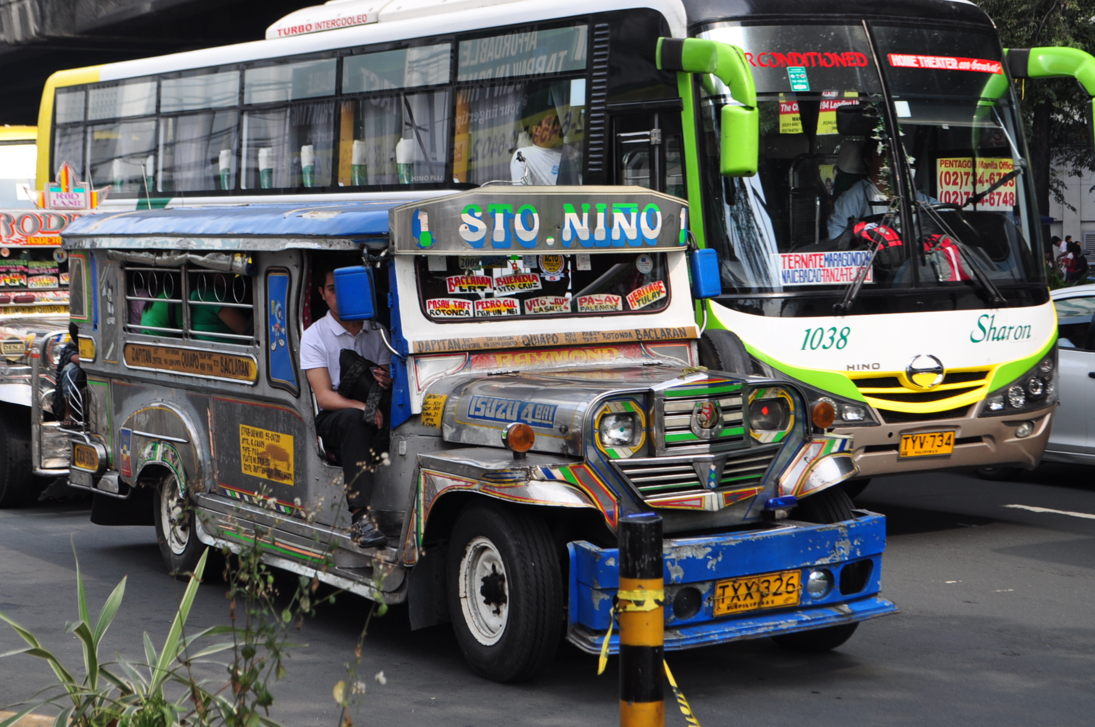 Blue and white jeepney with a green and white bus behind it