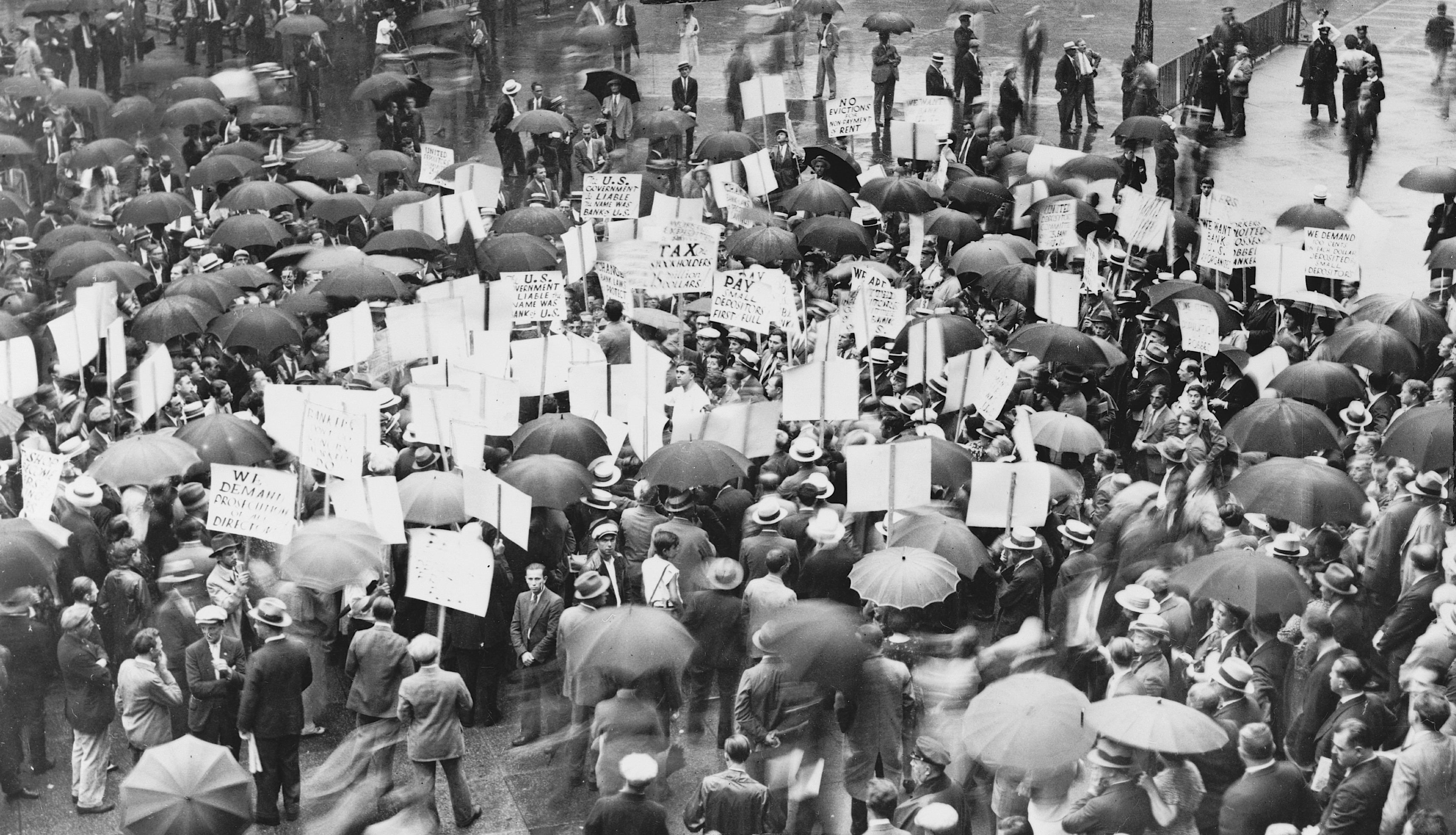 1931 - Crowd of depositors gather in the rain outside Bank of United States after its failure.