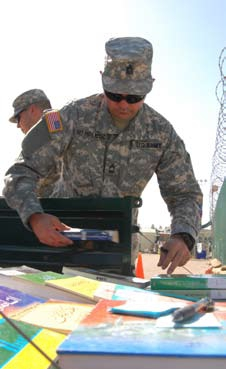 English: A Joint Task Force Guantanamo Trooper displays reading materials from the JTF library for detainees to choose from. The library holds 8000 books and magazines in English, Pashtu and Arabic. – JTF Guantanamo photo by Navy Petty Officer 2nd Class Patrick Thompson