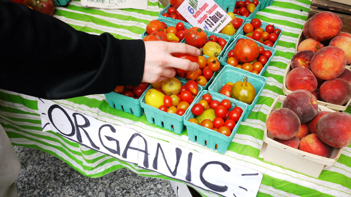 hand grabbing tomato at farmers market with organic sign on the table