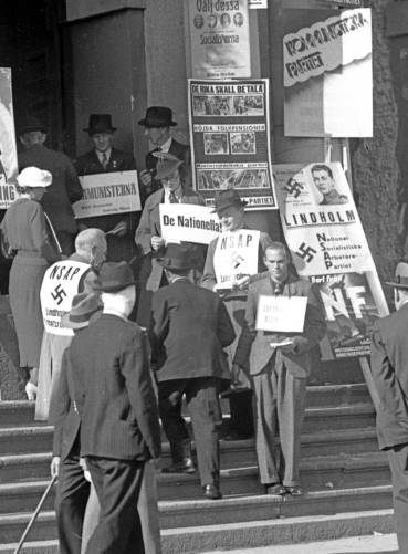 A typical feature of Swedish elections is the handing out of party ballot papers by activists of the different parties outside polling stations on election day. Photo from the 1936 election.
