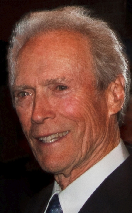 A headshot of an older man is looking to the left while smiling