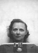Mug shot of woman with glasses in suit The number V-56 appears in front of him.