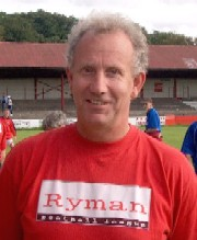 "A middle-aged man with curly grey hair, wearing a red T-shirt with ""Ryman Football League"" printed on it"