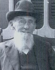 A black-and-white photograph of an elderly man with a long white beard wearing a hat