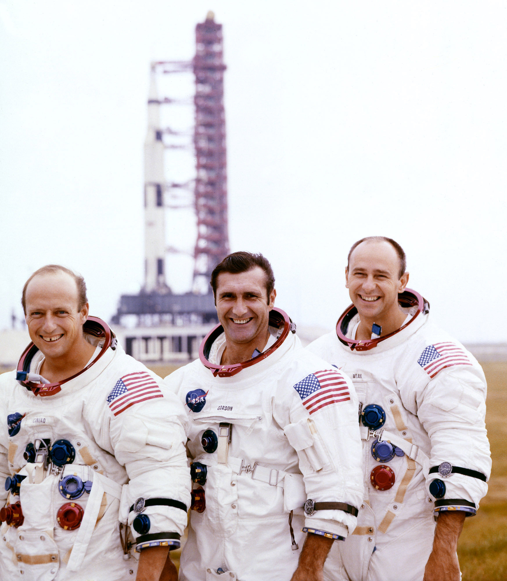 Pete Conrad, Dick Gordon, and Alan Bean pose with their Apollo 12 Saturn V Moon rocket in the background on the pad at Cape Canaveral on October 29, 1969