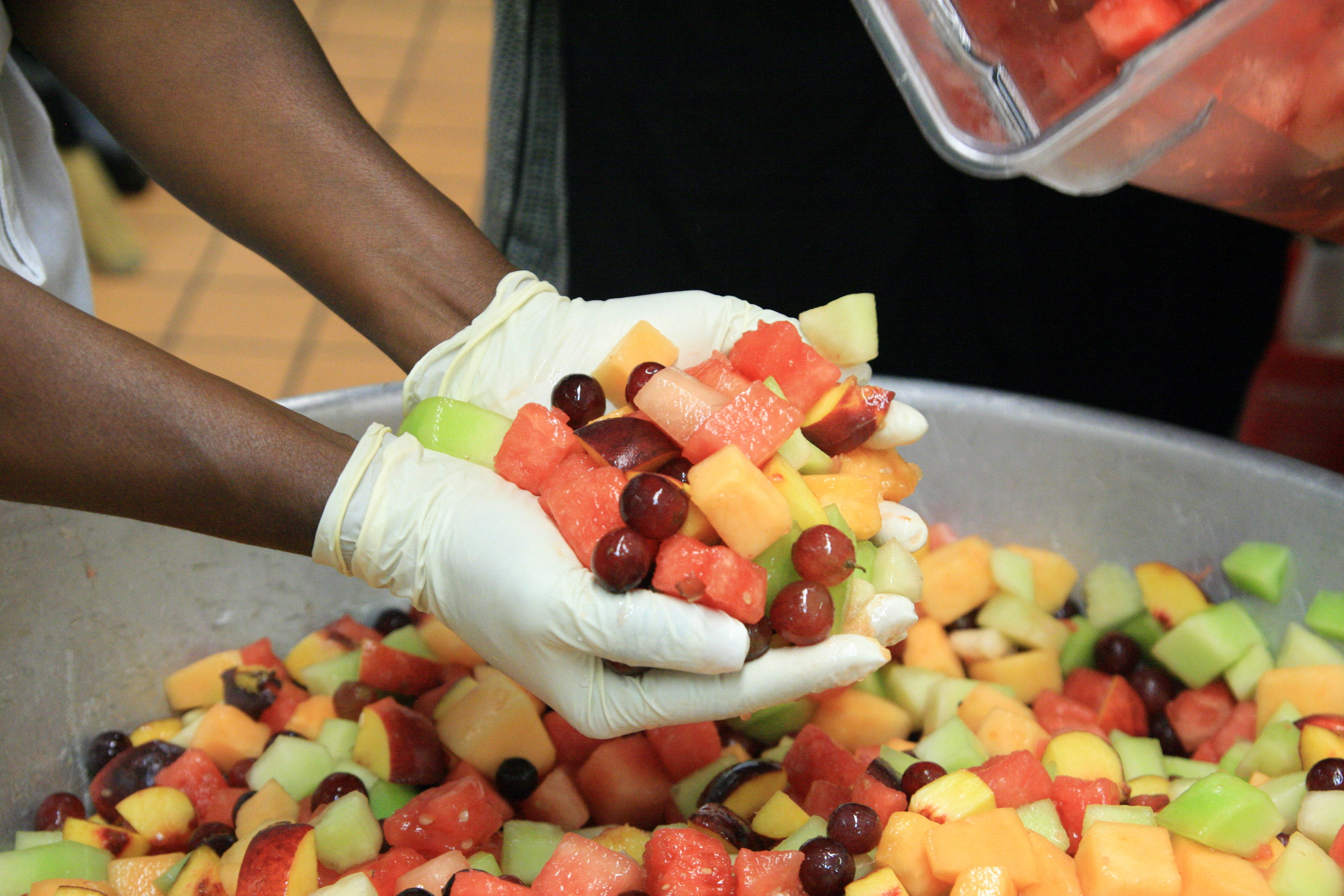 Gloved hands mixing a bowl of fruit salad