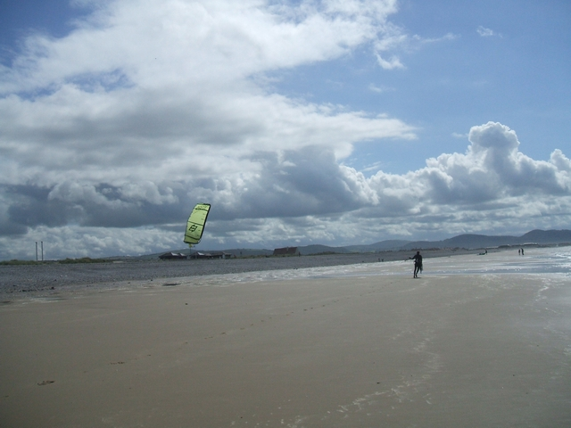 Kinmel Dunes Nature Reserve A kite surfer wanders back along the beach on a blustery day.