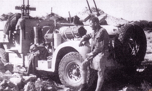 truck with an array of machine guns mounted, with a man in the foreground