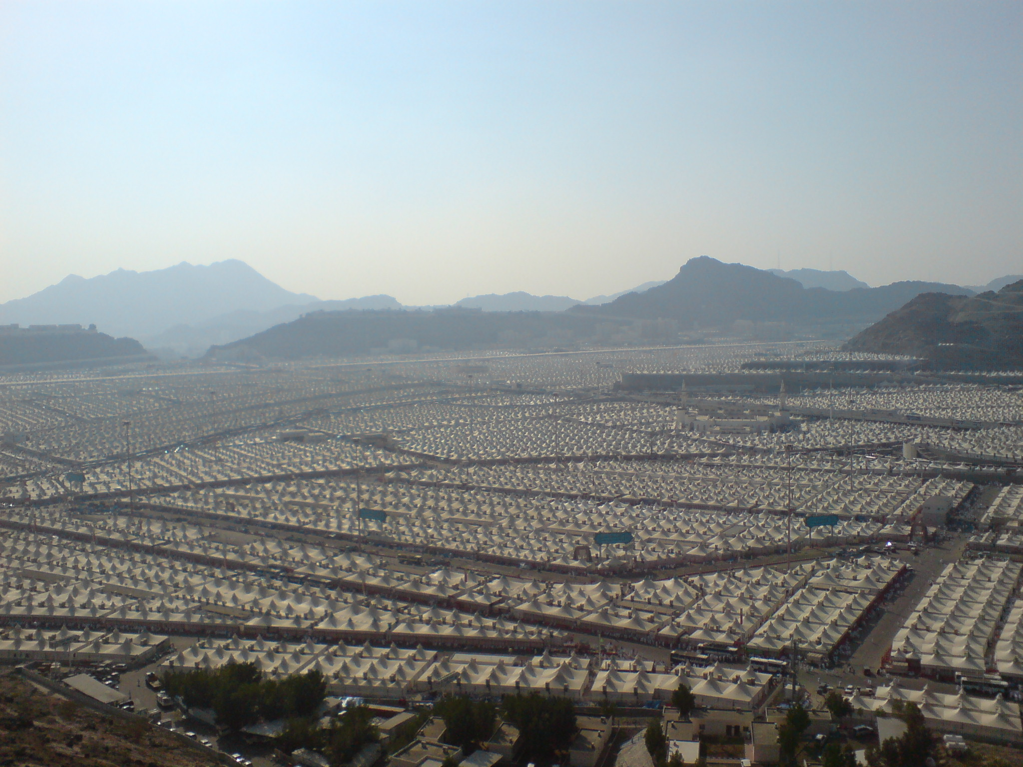 A wide view of the tent city of Mina, with rows of white tents in between streets.
