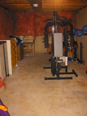 an unfinished basement used for storage and exercise equipment