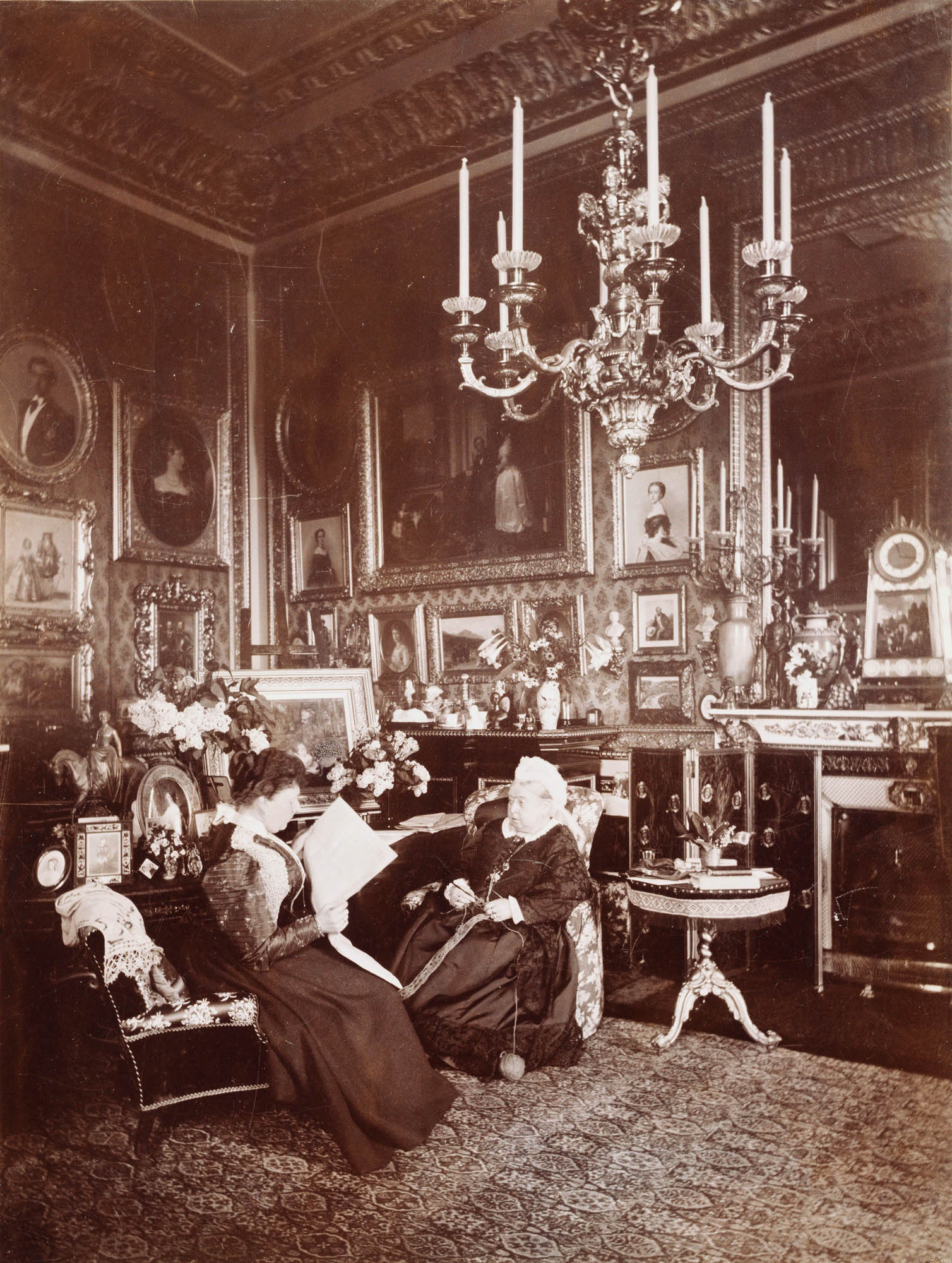 A black and white photograph of an elderly Victoria sat alongside a younger woman (Beatrice) reading a newspaper. The room is ornately decorated, with a number of photographs, paintings and a large chandelier hanging from the ceiling.