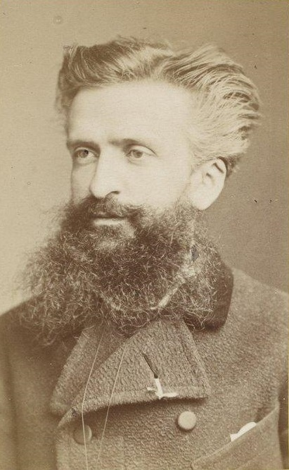 Portrait of a man in his thirties with swept back hair and a large beard