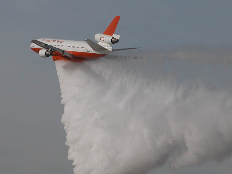 A three-engine red-and-white cargo plane in-flight, releasing a large quantity of water from its undercarriage storage tanks. The water trails behind the aircraft in a continuous, fan-shaped drop pattern.