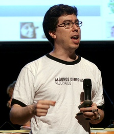 "waist high portrait wearing a T-shirt reading ""Algunos Derechos Reservados"", holding a microphone hand and a marker in the other"