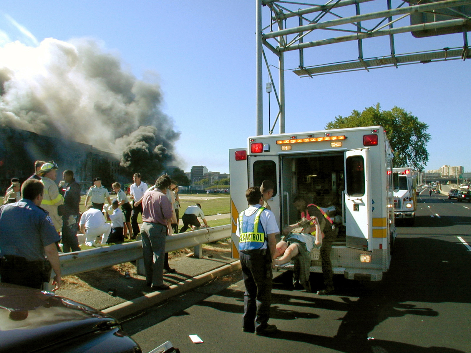 An injured victim is being loaded into a paramedic van with the burning Pentagon in the background