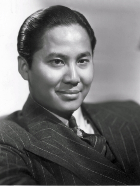 Head and shoulders publicity shot of a young, smiling man, short hair slicked back and wearing a suit and tie.