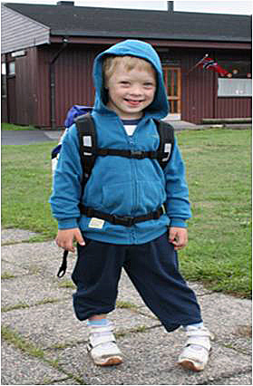 A boy wearing a jacket and a backpack