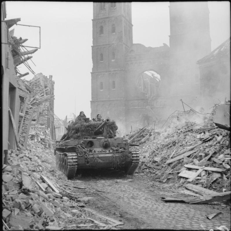 A Cromwell tank of 11th Armoured Division advances through the rubble of Uedem
