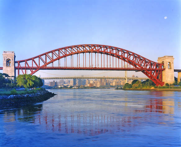 A lovely red bridge arches over a river between two stone towers with the city skyline in the background