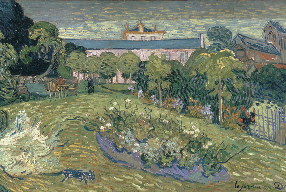 An enclosed garden surrounded by trees, with a large house in the background, and another house off to the right. On the green lawn foreground is a cat, in the center of the lawn is a bed of flowers and at the rear of the lawn is a bench, a table and a few chairs. Nearby is a lone figure