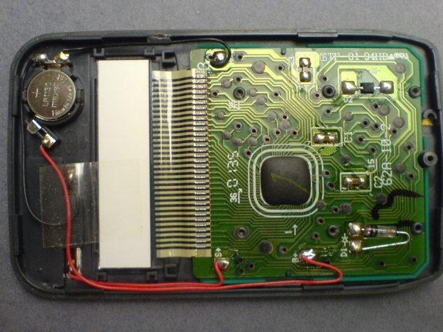 The interior of a newer (ca. 2000) pocket calculator. The processor chip (not visible) in the centre is covered with dark epoxy