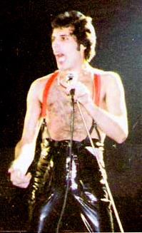 Photographie couleur d'un homme qui chante dans un micro et lève le bras droit.