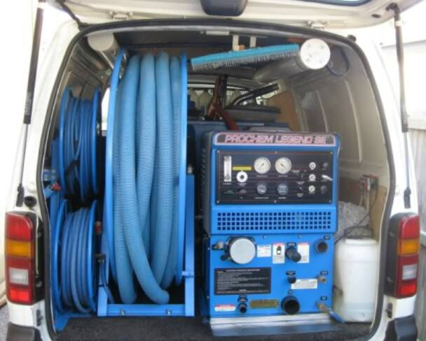 carpet cleaners vehicle with hoses, chemicals and machinery