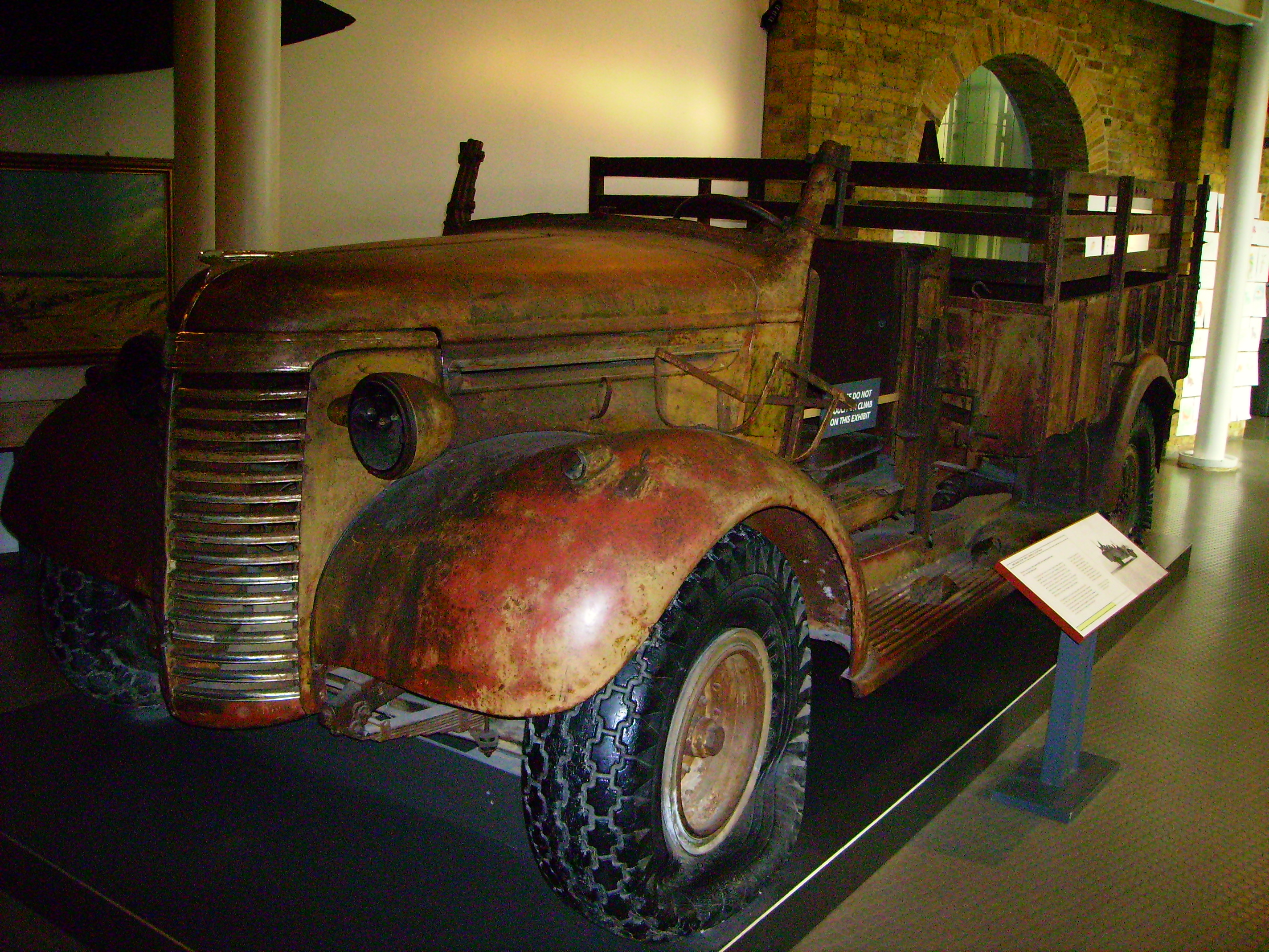 A three-quarter view of a small, four-wheel truck, it has some rust but it largely intact