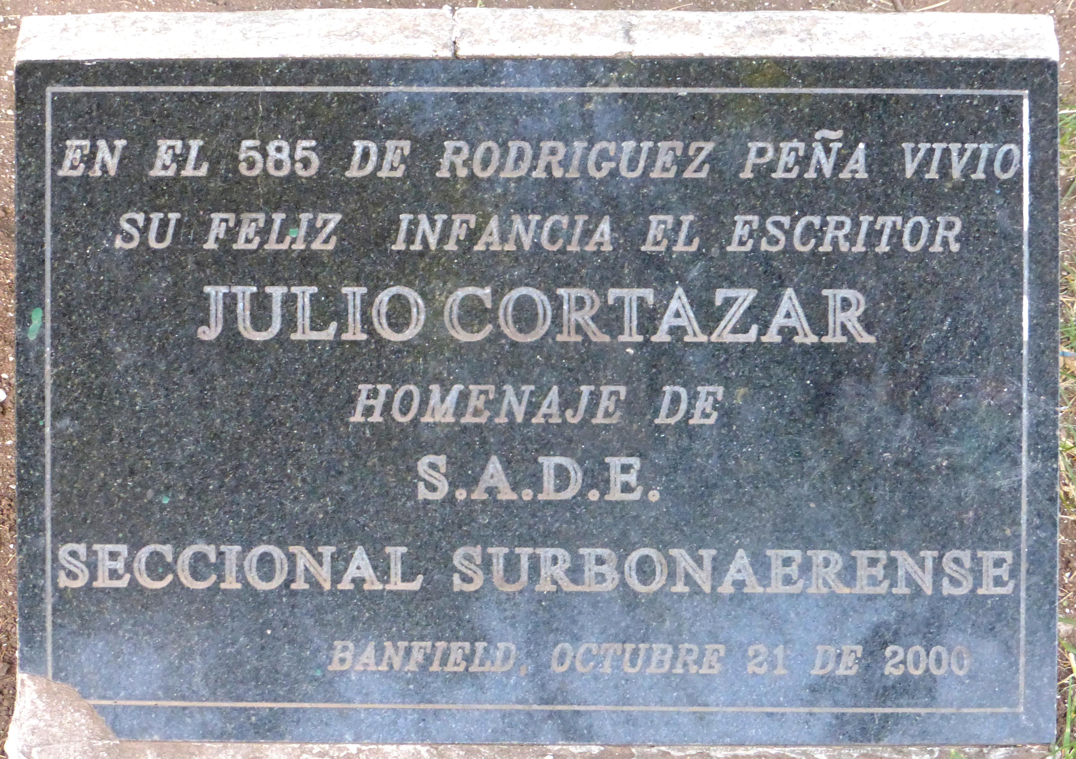 Placa en la plaza Alfredo De Angelis de la localidad de Banfield, que recuerda la infancia del escritor en dicha ciudad.