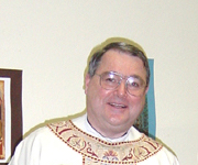 A bespectacled man wearing a white chasuble with beige and burgundy ornamentation around the neckline