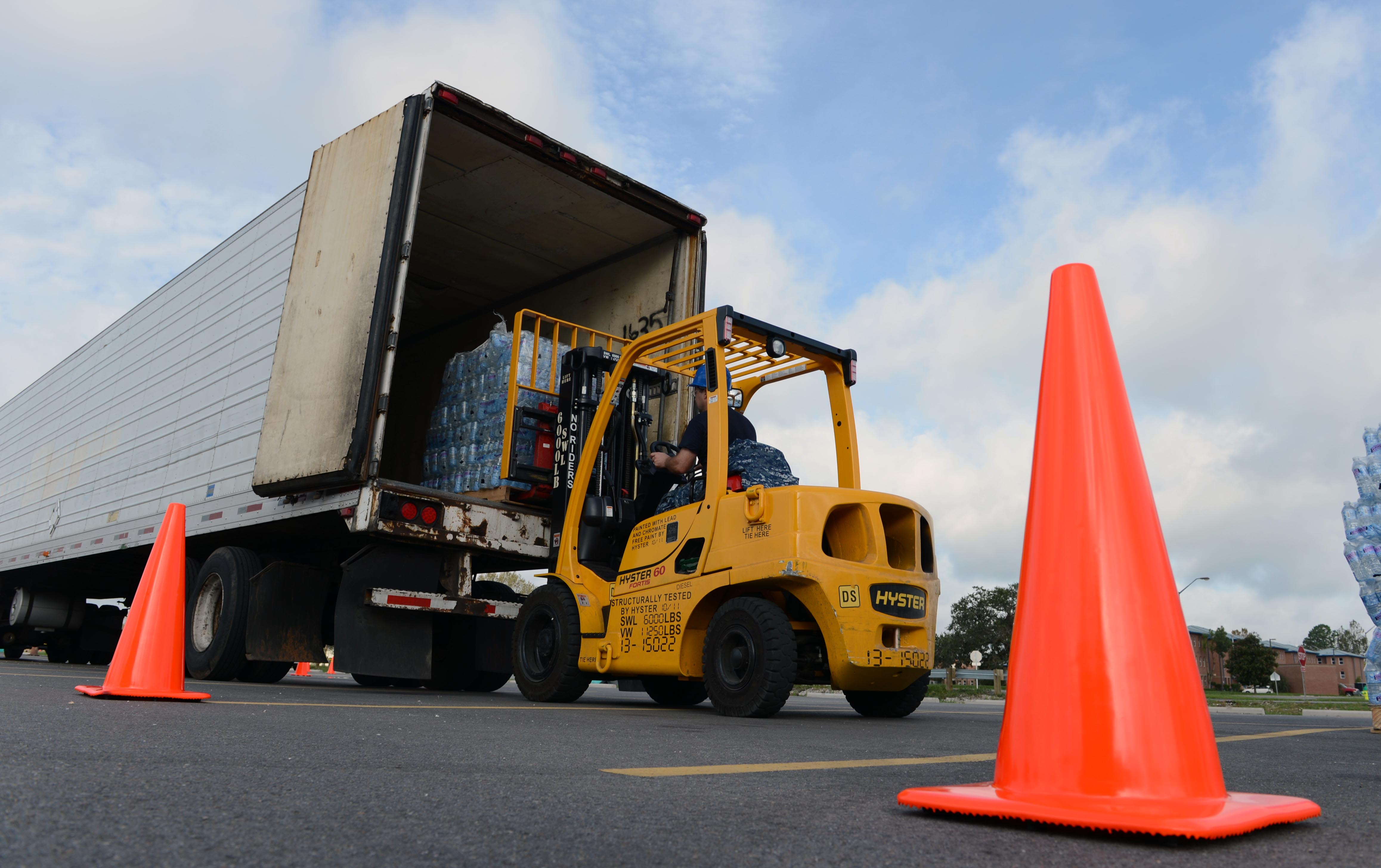 file a u s sailor uses a forklift to unload bottled water from a
