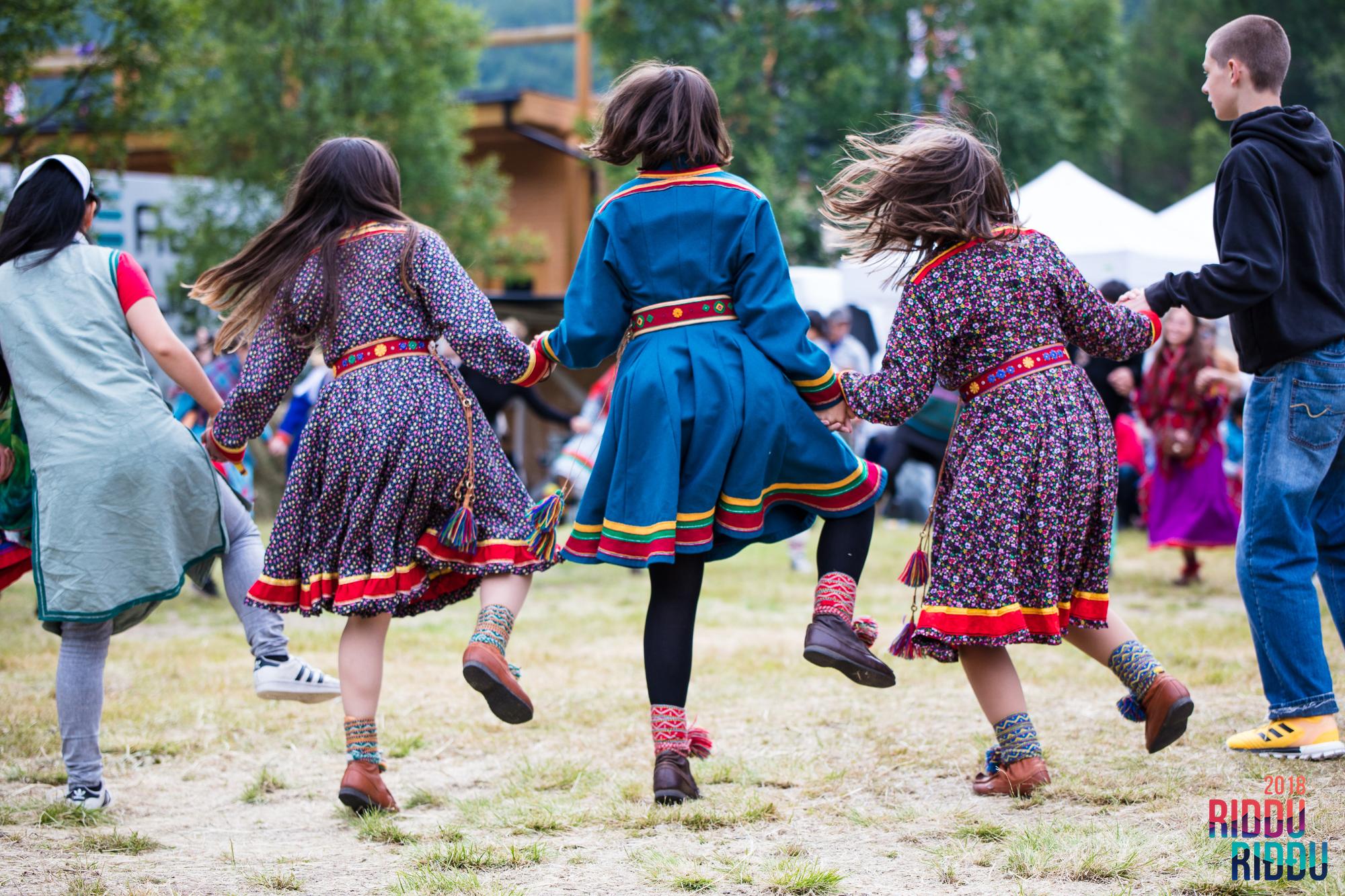 Kolme nuorta naista perinteinen saamenpuku yllään tanssii Riddu Riđđu -festivaaleilla vuonna 2018