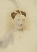 A photograph of Margaret Macpherson Grant, dressed in a white shirt and wearing a necklace around her neck