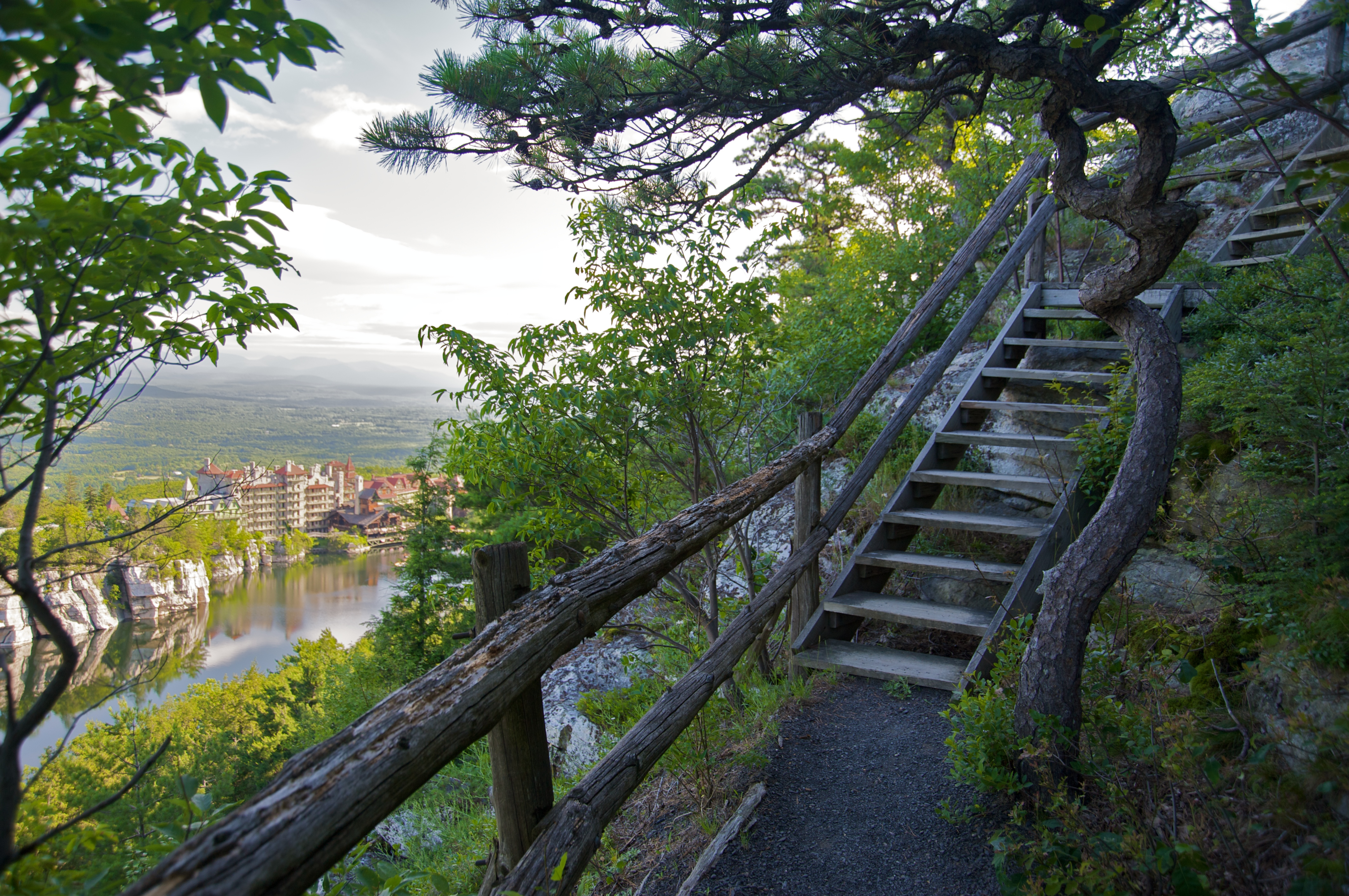 Staircase in woods overlooking lake and castle