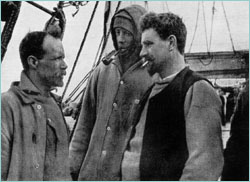 Three men in well-worn clothing stand on the deck of a ship. Man on right is thickset, bearded, with cigarette in mouth. Man in centre is hooded; man on left, also bearded and with receding hair, is shown right profile.