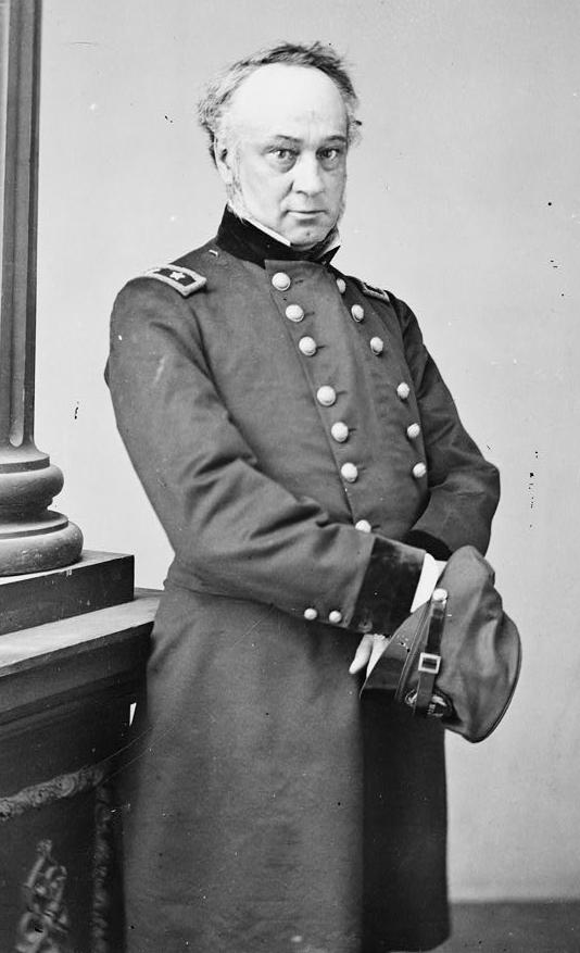 A black and white image of the general standing in uniform