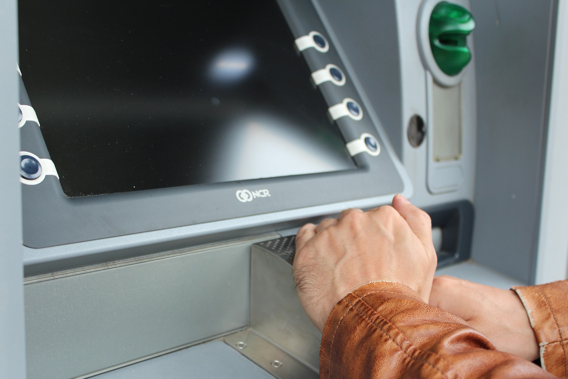 A person concealing their PIN entry at an ATM