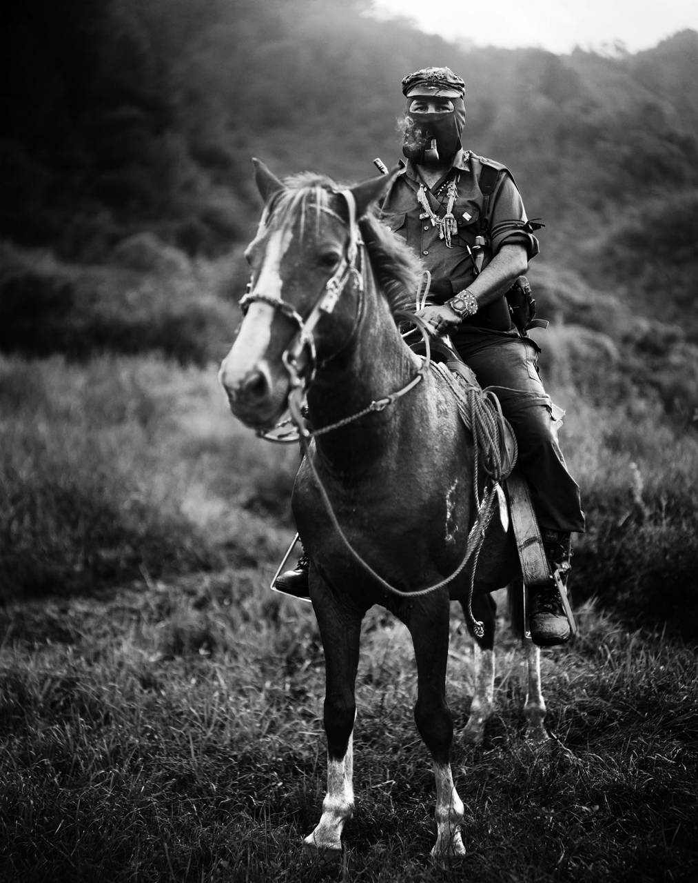 Subcomandante Marcos, smoking a pipe atop a horse in Chiapas, Mexico in 1996.