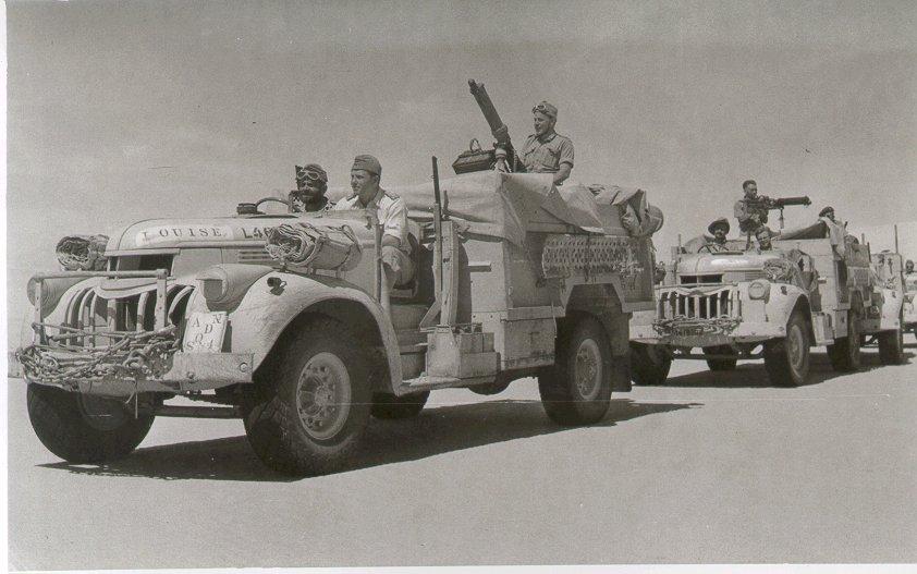 vehicles in convoy, each crewed by three men, in a desert terrain