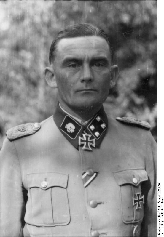 alt=A black-and-white photograph of a man wearing a military uniform and neck order in shape of an Iron Cross. His hair is combed back and his facial expression is determined.