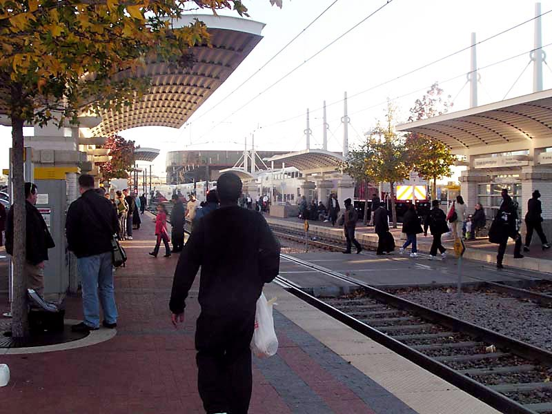 Numerous passengers walking and waiting along the tracks at the side platforms of the station with a train and arena at rear.