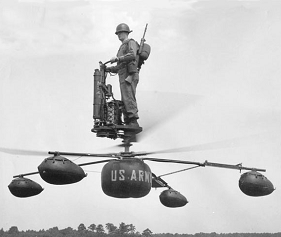 An infantryman in khaki uniform and steel helmet, a rifle slung on his back, stands atop a platform mounted above two counter-rotating rotors and four landing-gear legs of a strange helicopter-like craft, holding the steering handlebars of the vehicle.